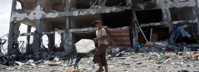 A Palestinian child withn a kite in front of the destroyed Al-Nada towers in Beit Hanoun, North Gaza, August 4, 2014. The towers had 90 flats. So far, Israeli attacks have killed at least 1,870 Palestinians, and injured 9470 since the beginning of the Israeli offensive.